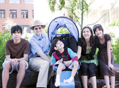 Father sitting with his biracial children and disabled son — ストック写真
