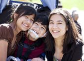 Disabled boy in wheelchair surrounded by big sisters, smiling — Stock Photo