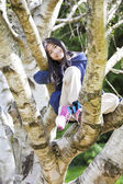Young girl sitting in birch tree, smiling — Stock Photo