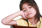 Sad nine year old girl sitting on chair, bored. — Stock Photo