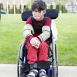 Disabled little boy in wheelchair outdoors — Stock Photo #26392539