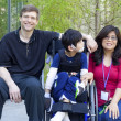 Disabled child in wheelchair with his parents — Stok fotoğraf