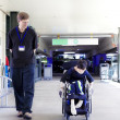 Father walking with disabled son in wheelchair to the hospital — 图库照片