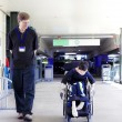 Father walking with disabled son in wheelchair to the hospital — Stockfoto