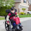 Disabled little boy in wheelchair outdoors — Stock Photo #26392841