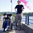 Father walking with disabled son out on lake pier — Stock Photo #26392975
