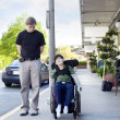 Father walking next to disabled son in wheelchair through town — Foto Stock