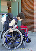 Disabled kindergartener in wheelchair on playground at recess — Stock Photo