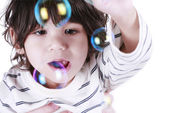 Toddler boy playing with bubbles — Stock Photo
