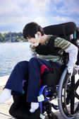 Disabled little boy in wheelchair out on pier by lake — Stock Photo
