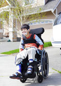 Happy little disabled boy in wheelchair — Stock Photo