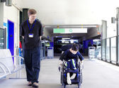 Father walking with disabled son in wheelchair to the hospital — Stock Photo