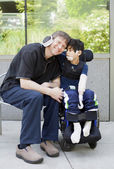 Disabled boy hugging father while waiting at hospital — Stock Photo