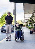 Father walking next to disabled son in wheelchair through town — Stock Photo