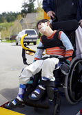 Disabled boy on school bus wheelchair lift — Stock Photo