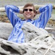 Stock Photo: Min forties leaning back against log on beach