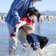 Father helping disabled son walk in the ocean waves on beach — Stock Photo