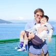 Stock Photo: Father holding disabled son in arms on deck of ferry boat.