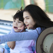 Teen sister taking care of disabled little brother, pointing off — Stock Photo