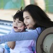Teen sister taking care of disabled little brother, pointing off — Stockfoto