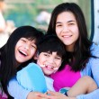 Stock Photo: Two sisters taking care of disabled little brother