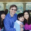 Stock Photo: Father with his biracial children, holding disabled son on ferry