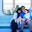 Stock Photo: Interracial couple holding disabled son on ferry boat deck