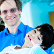 Handsome father in forties holding disabled son in arms — Stock Photo