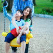 Big sister holding disabled brother on special needs swing at pl — Stok fotoğraf