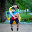 Stock Photo: Big sister holding disabled brother on special needs swing at pl