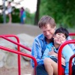 Father holding disabled son on merry go round at playground — Stock Photo