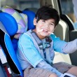 Handsome disabled six year old boy smiling in carseat — Stock Photo