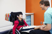Disabled boy in wheelchair with his doctor — Stock Photo