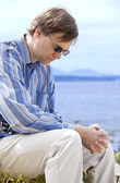 Handsome man in forties praying by side of lake — Stock Photo