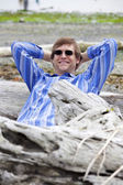 Man in forties leaning back against log on beach — Stock Photo