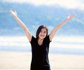 Happy young woman on beach, arms outstretched — Stock Photo