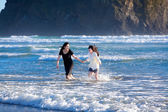 Two sisters running in the waves of the ocean together — Stock Photo