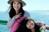 Two happy girls smiling on ferry deck with ocean in background — Stock Photo