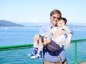 Father holding disabled son in arms on deck of ferry boat. — Stock Photo