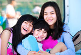Two sisters taking care of disabled little brother — Stock Photo