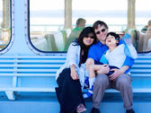 Interracial couple holding disabled son on ferry boat deck — Stock Photo
