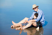 Father playing with disabled son on beach, holding him upright — Stock Photo