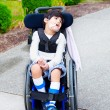 Foto Stock: Seven year old biracial disabled boy in wheelchair