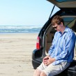 Caucasian man in car at beach, unhappy, worried expression — Stock Photo