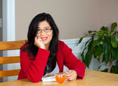Asian woman in early forties sitting at table with drink — Stock Photo