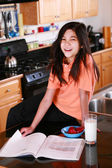 Young girl on kitchen counter with glass of milk — Stock Photo