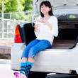 Preteen girl sitting on back car bumper eating lunch — Stock Photo #34389615