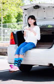 Preteen girl sitting on back car bumper eating lunch — Stock Photo