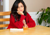 Asian woman in early forties sitting at table with drink, depres — Foto Stock