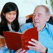 Elderly man and little girl reading Bible together — Stock Photo